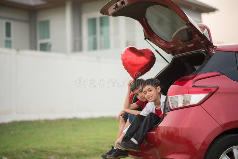 Rapazes pequenos que dão o coração do balão a seu amor de mãe imagem de stock