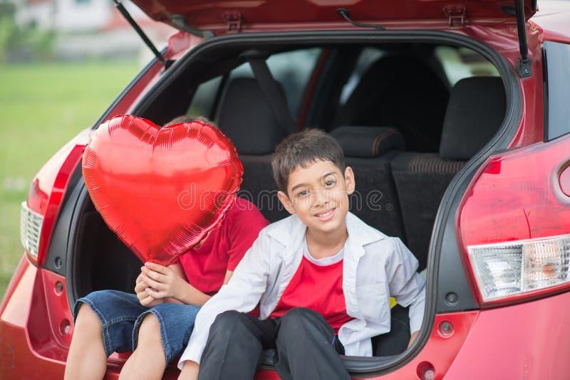 Rapazes pequenos que dão o coração do balão a seu amor de mãe fotos de stock