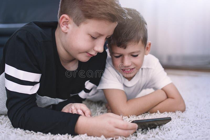 Rapazes pequenos que usam o smartphone no tapete imagem de stock royalty free