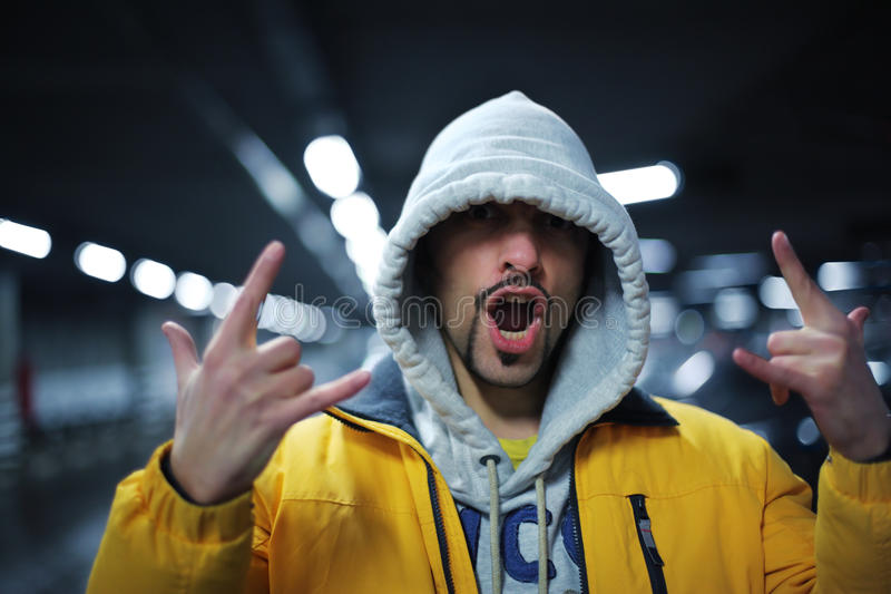 Raper gesture. Portrait of young man in hoodie showing intimidating gesture. Shallow DOF royalty free stock photo