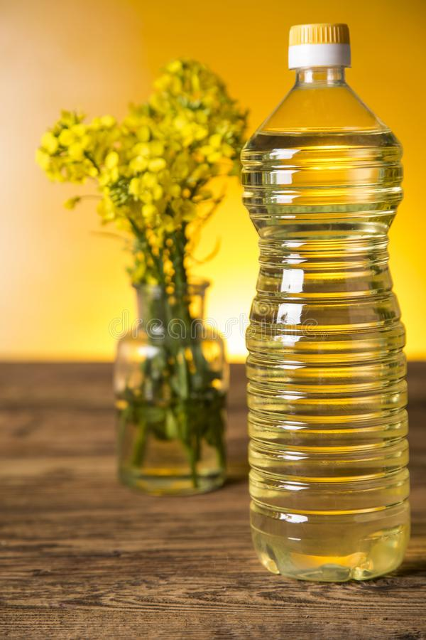 Rapeseed flowers and rapeseed oil in a bottle on the table royalty free stock photography