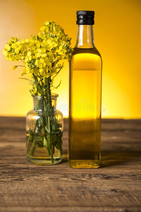 Rapeseed flowers and rapeseed oil in a bottle on the table royalty free stock photos
