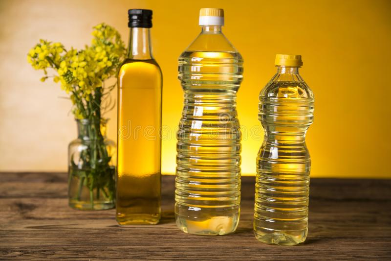 Rapeseed flowers and rapeseed oil in a bottle on the table stock photos
