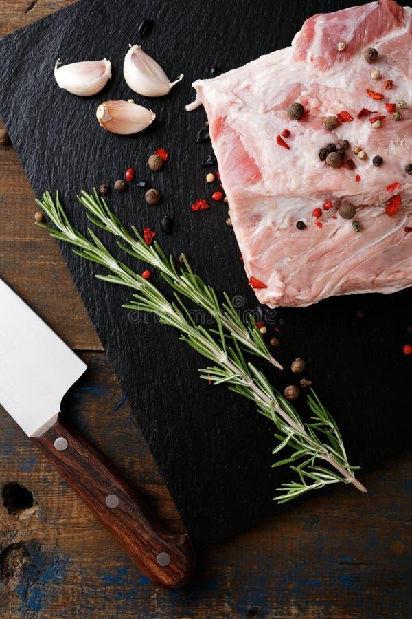 Rapiécez le bifteck de la viande de porc crue avec les épices, l'ail et le romarin images stock