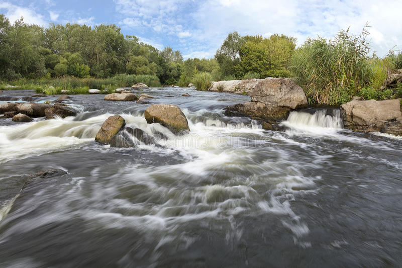 The rapid flow of the river, rocky coasts, rapids, bright green vegetation and a cloudy blue sky in summer - a frontal view. The rapid flow of the river, rocky royalty free stock images