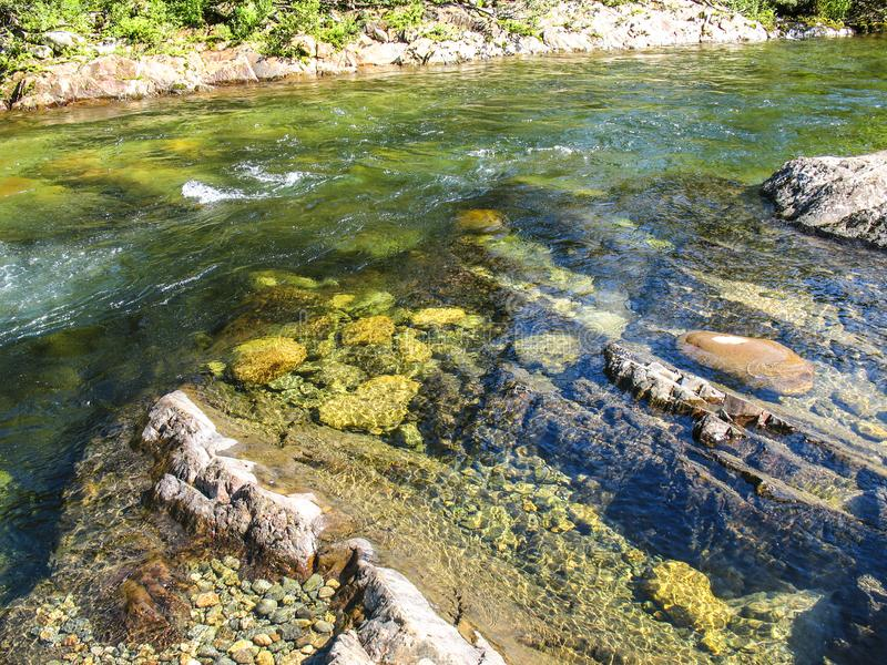 Rapid stream of mountain river with clean transparent water and colorful stones and pebbles on bottom stock image