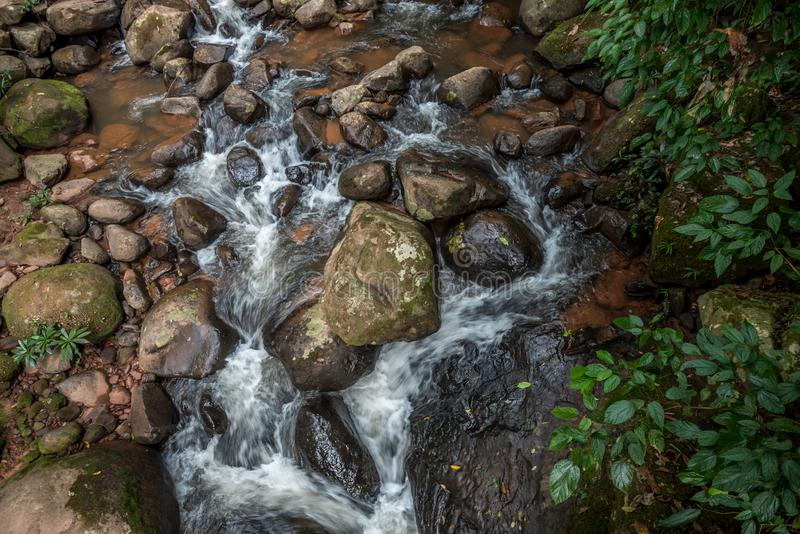Rapid water flowing over natural rocks in a mountain stream. stock photography