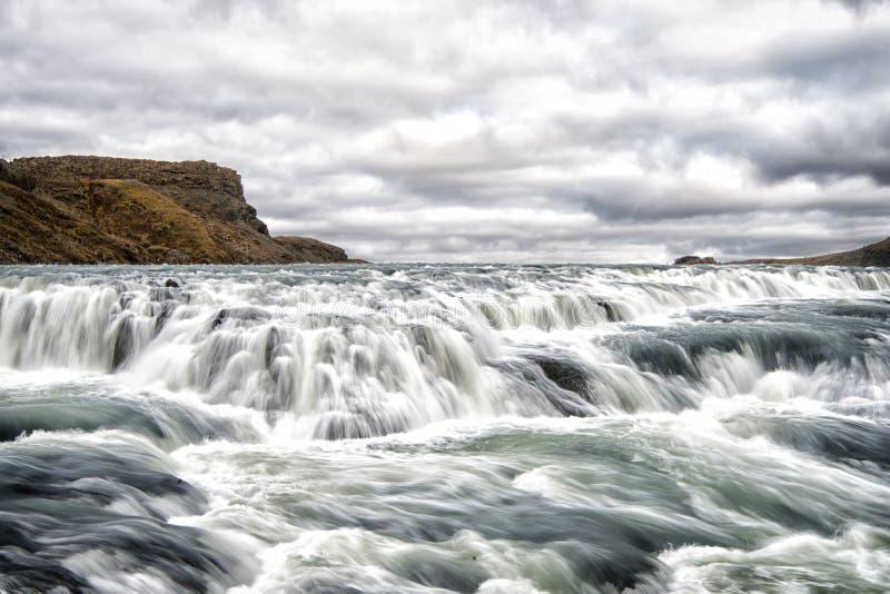 Rapide de rivière à reykjavik, Islande Écoulement de courant de l'eau L'eau tombe sur le ciel nuageux Vitesse et turbulence Horiz image stock