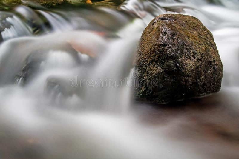 Rapids On The Boyne River Softened By Long Exposure. A moss covered rock sits solid in the fast moving waters of the Boyne River, just upstream from Hoggs Falls royalty free stock images