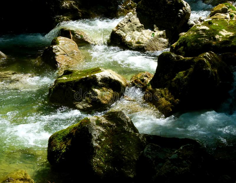 Rapids in the wild brook with boulders in the water royalty free stock image