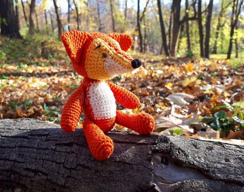 A raposa feita malha do brinquedo senta-se em um log na perspectiva da floresta do outono foto de stock