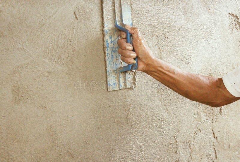 Rappa en husvägg konkret arbetare för murbruk på väggen av nytt royaltyfria foton