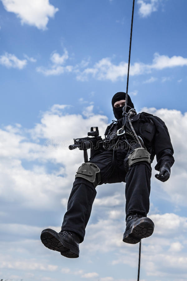 Rappeling assault. Special forces operator during assault rappeling with weapons stock image