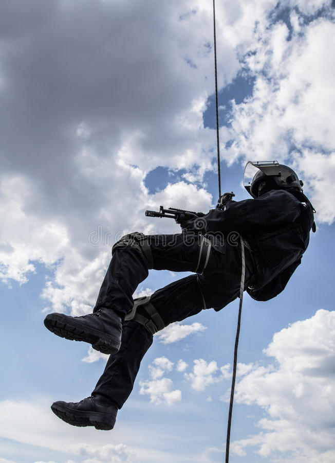 Rappeling assault. Special forces operator during assault rappeling with weapons stock photography