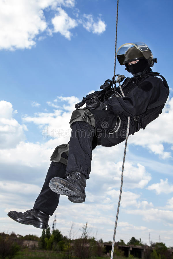 Rappeling assault. Special forces operator during assault rappeling with weapons royalty free stock images