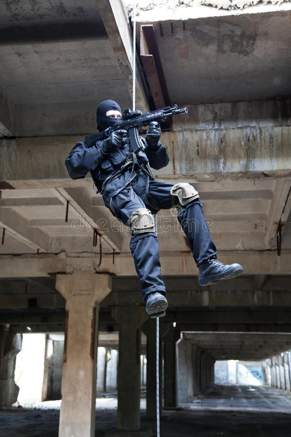 Rappeling assault. Special forces operator during assault rappeling with weapons stock photos