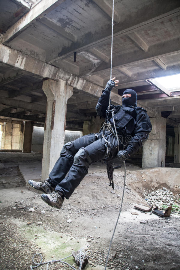 Rappeling assault. Special forces operator during assault rappeling with weapons royalty free stock photography