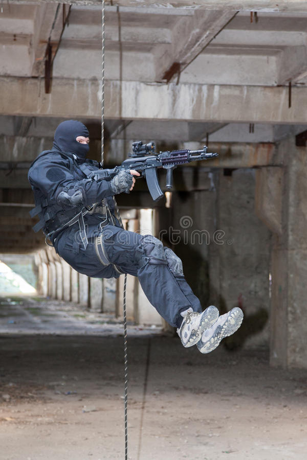Rappeling assault. Special forces operator during assault rappeling with weapons stock photo