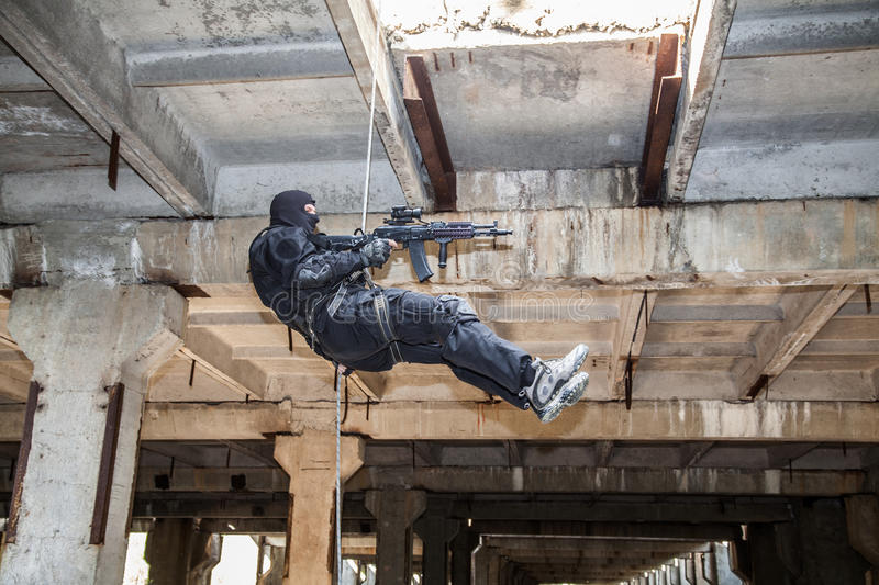Rappeling assault. Special forces operator during assault rappeling with weapons royalty free stock photos