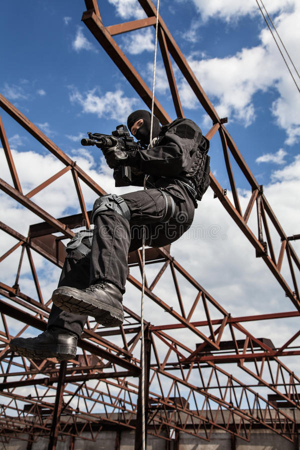 Rappeling assault. Special forces operator during assault rappeling with weapons royalty free stock photo
