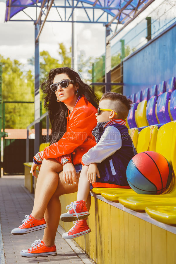 Rapper attitude rap singer hip Hop Dancer. Performing. Stylish women and little boy posing at basketball court royalty free stock photography