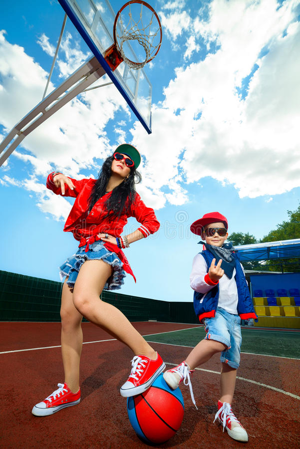 Rapper attitude rap singer hip Hop Dancer. Performing. Stylish women and little boy posing holding their feet on ball at basketball court royalty free stock photography