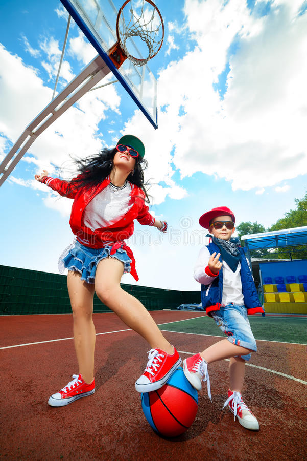 Rapper attitude rap singer hip Hop Dancer. Performing. Stylish women and little boy posing holding their feet on ball at basketball court royalty free stock image