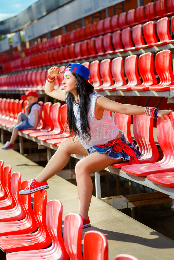 Rapper attitude rap singer hip Hop Dancer. Performing. Stylish women and little boy sitting in the stands of stadium royalty free stock image