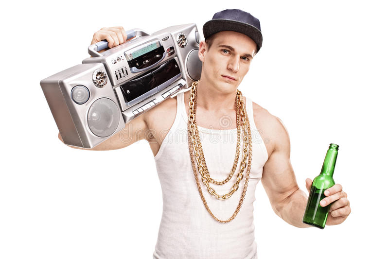 Rapper carrying a ghetto blaster and holding beer. Young male rapper carrying a ghetto blaster over his shoulder and holding a bottle of beer isolated on white royalty free stock photography