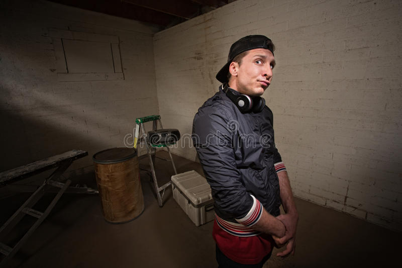 Rapper with Folded Arms. Urban musician with arms folded in basement stock photo