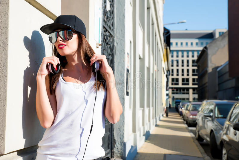 Rapper girl with headphones in a european city. A beautiful young Hip Hop Rapper girl with Headphones in a urban environment.r stock photo