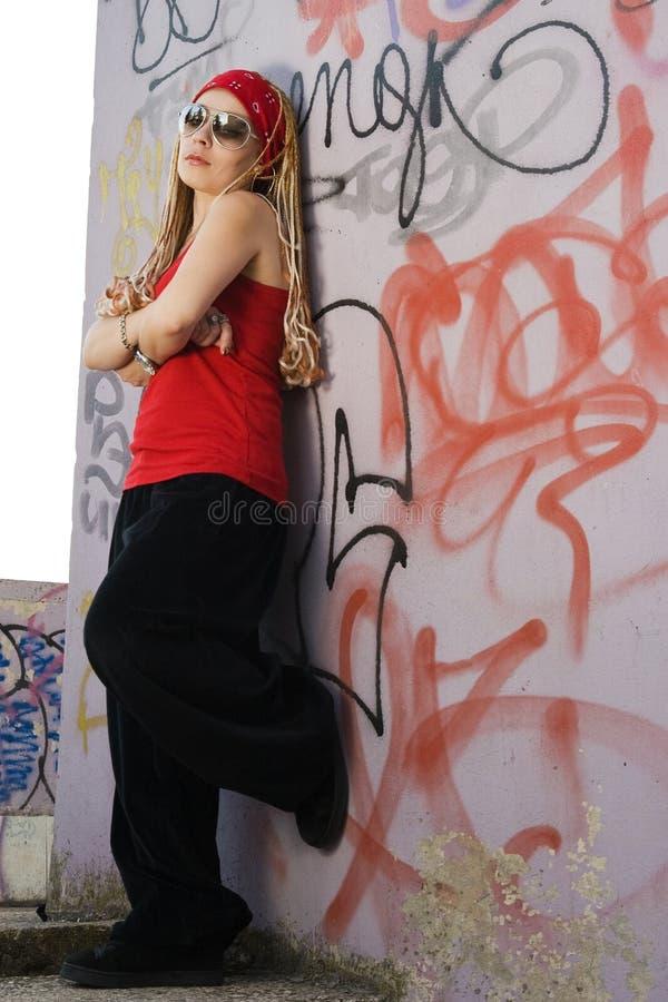 Rapper girl posing at graffiti sprayed wall royalty free stock photography