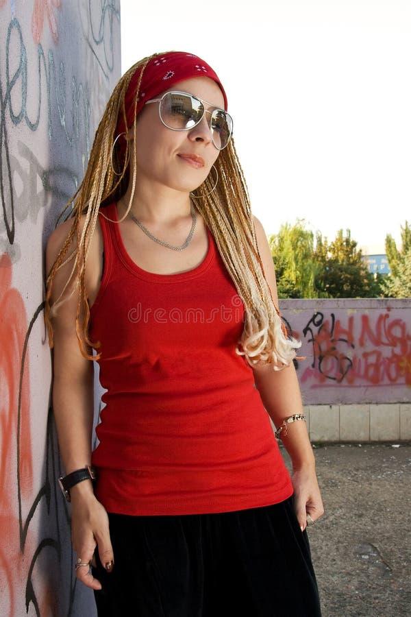 Rapper girl posing at sprayed wall