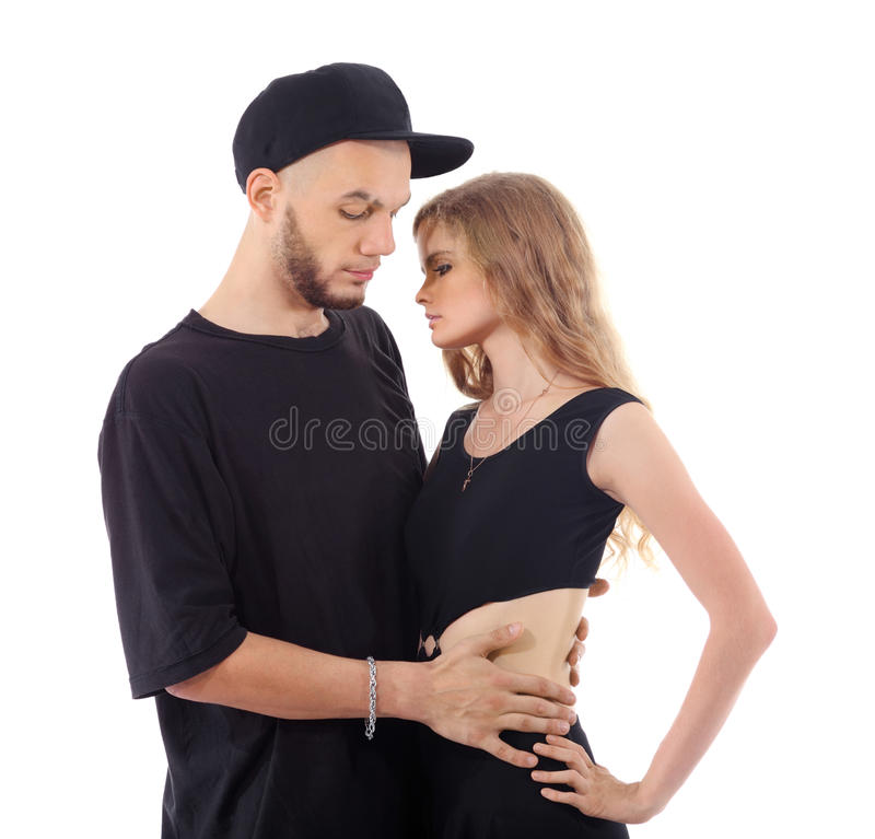 Rapper hugs graceful girl isolated. Rapper wearing black t-shirt and hat hugs graceful girl isolated on white background stock photography