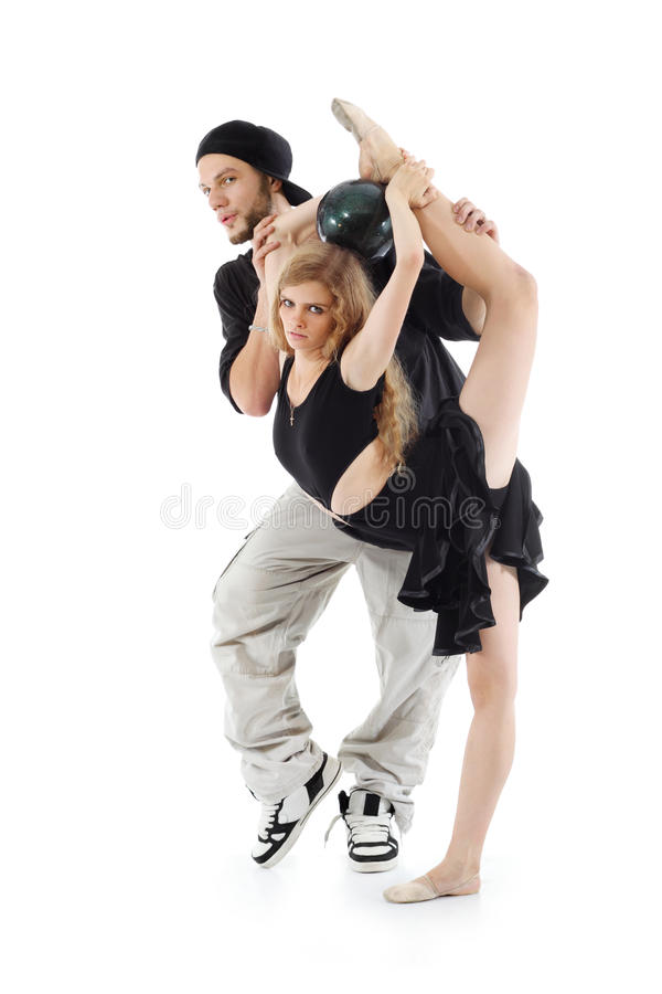 Rapper keeps gymnast girl which stands on one leg with ball. Rapper keeps beautiful gymnast girl which stands on one leg with ball on head and other leg held up stock photo