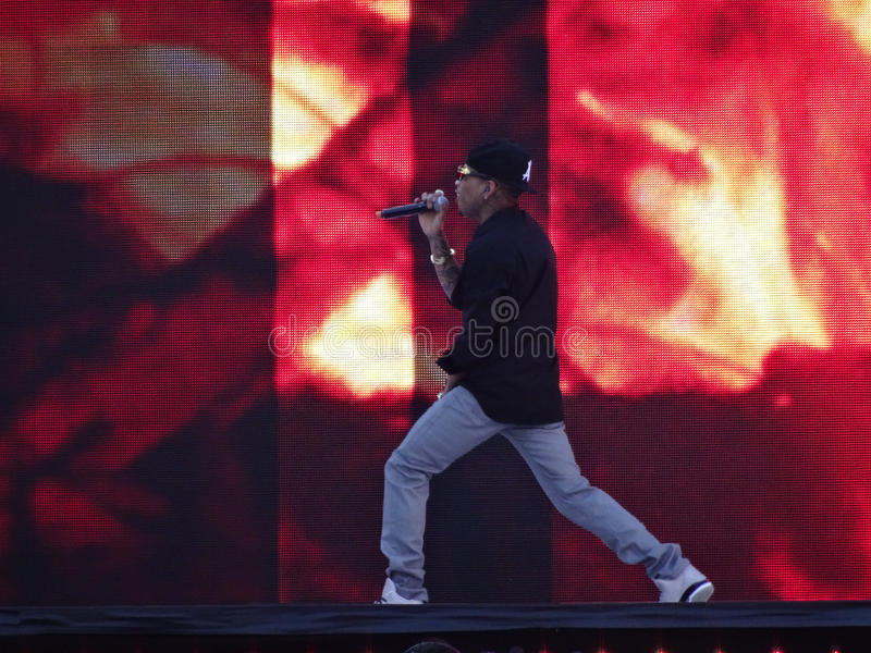 Rapper Kid Ink sings into mic on stage. SANTA CLARA - MARCH 29: Rapper Kid Ink sings into mic on stage at Wrestlemania 31 at the Levi's Stadium in Santa Clara stock images