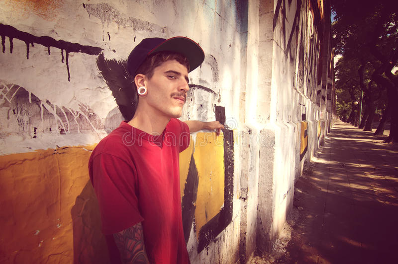Rapper leaning on a Wall. A young Rapper leaning against a wall stock photo