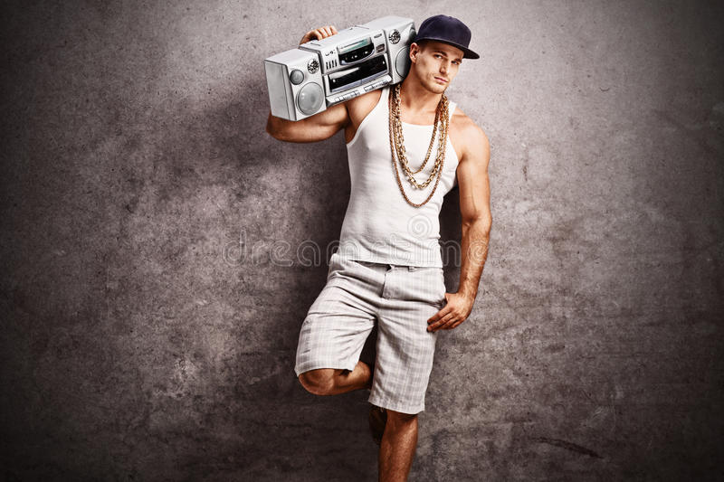Rapper listening to music from a ghetto blaster. Young male rapper in hip-hop outfit listening to music from a ghetto blaster and leaning against a rusty gray royalty free stock photography