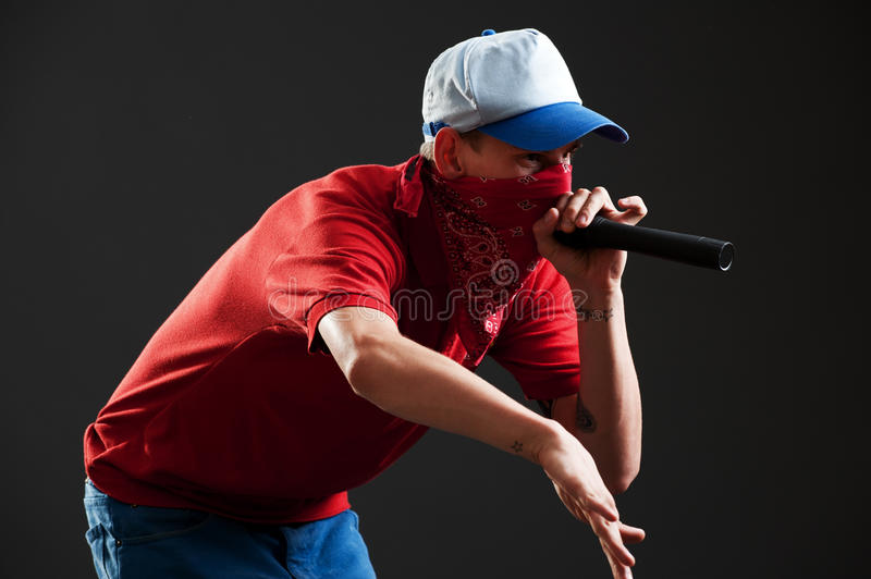 Rapper with microphone. Portrait of rapper with microphone over black background royalty free stock photography