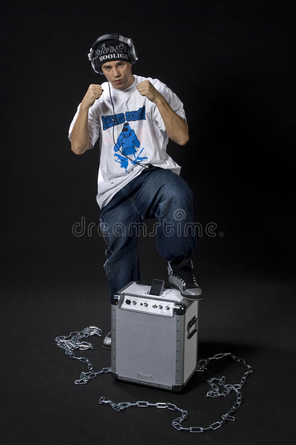 Rapper posture. Young DJ/rapper in defencive pose with his mobile sound system for ipod isolated on black background royalty free stock photos