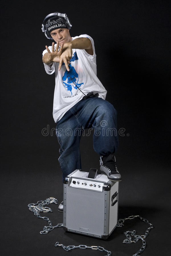 Rapper posture. Young DJ/rapper posing with his mobile sound system for ipod isolated on black background stock photos