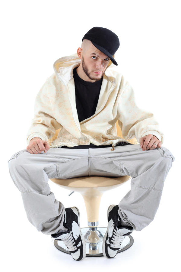 Rapper sits on chair and looks at camera stock photography