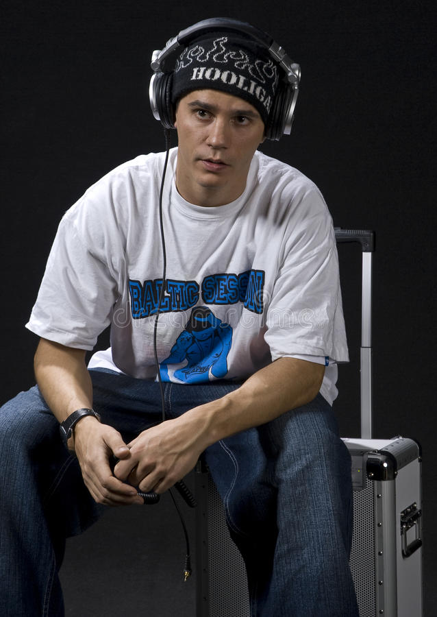 Rapper sitting. Young DJ/rapper sitting on his mobile sound system for ipod isolated on black background stock photos