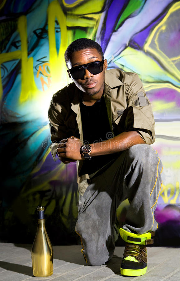 Rapper sitting near wall. Young afro-american man sitting in front of colorful graffiti wall royalty free stock photography