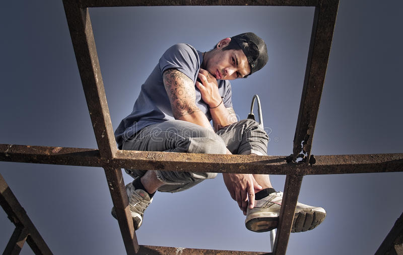 Rapper on structure. Young chilean rapper Luis Trujillo, member of the group KSaenCrew, posing on a rusted structure stock image
