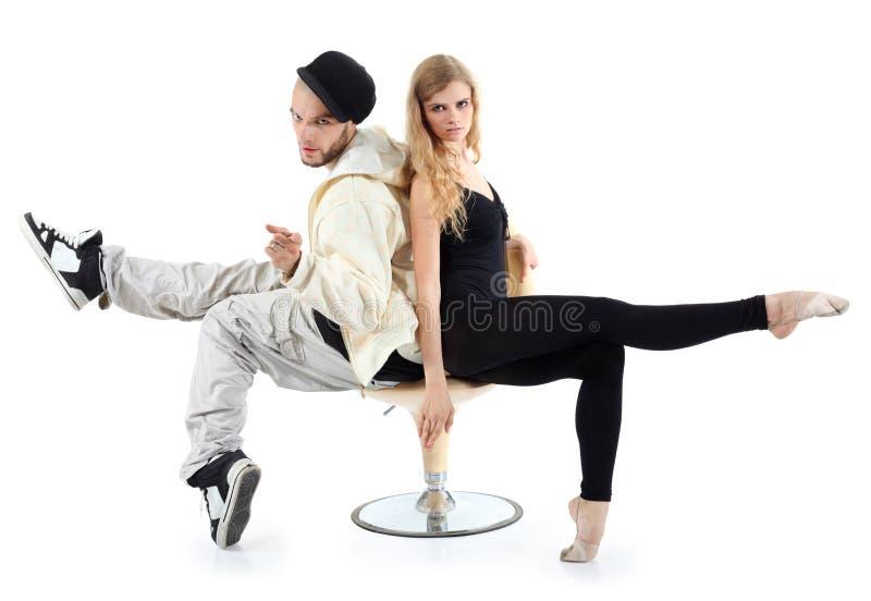 Rapper und Ballerina sitzen auf Stuhl und betrachten Kamera lizenzfreies stockfoto