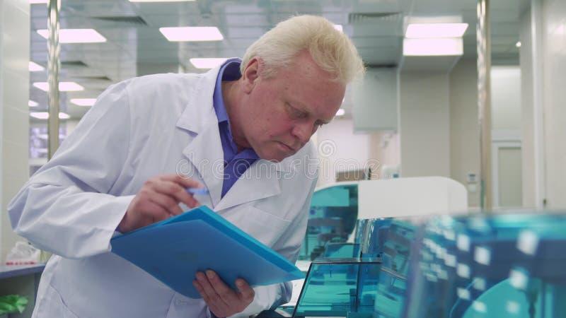 Rapport de notes d'homme au sujet de travail de machine de laboratoire image stock