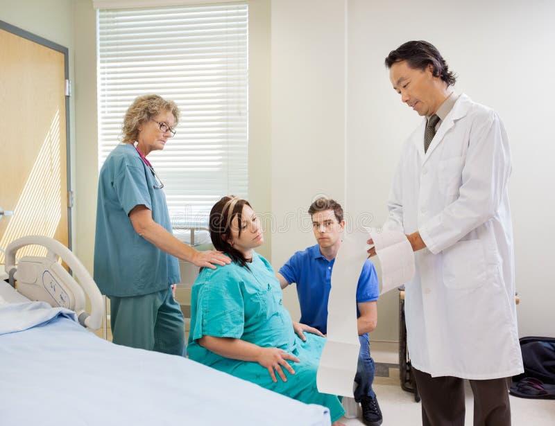 Rapport för doktor Explaining Fetal Monitor till gravid royaltyfria foton