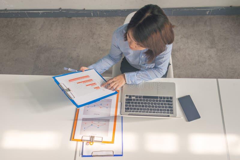 Rapport financier de lecture de femme asiatique de bureau dans la salle d'affaires photographie stock
