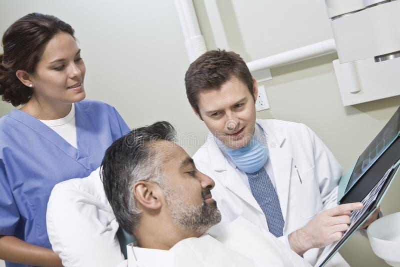 Rapporti dei raggi x di Explaining del dentista al paziente fotografia stock libera da diritti